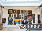 Dense gallery display of hanging paintings