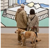 visually impaired visitors in front of a Lichtenstein artwork with a guide dog