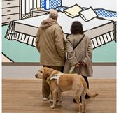 two people stand in front of a Lichtenstein artwork with a guide dog
