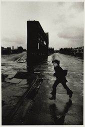 Black and white photo of a young boy running by a building