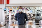 a member of staff wears a mask and stands behind the bar in the cafe