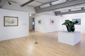 installation view showing a sculpture in the middle of a gallery space and artworks on the wall