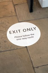 a floor sticker reads 'exit only, please follow the one way routes'
