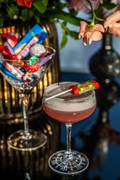 a dark pink cocktail with a lolly pop resting on the top of the glass