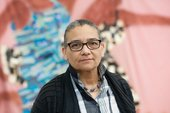 Portrait of Lubaina Himid with a painting in the backgound