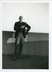 Len Lye stands in front of a low wall