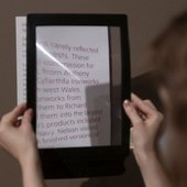 a close up of someone holding a magnifier over a wall text.
