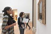 A teacher looking at an artwork in a gold frame