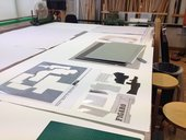 A paper collage replicating the original Picasso under construction on a work table surrounded by paper and a cutting blade