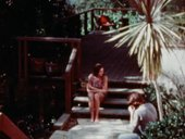 A woman and a man sit near the entrance of a California home