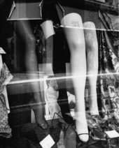 A black-and-white image of women's hosiery displayed in a shop window