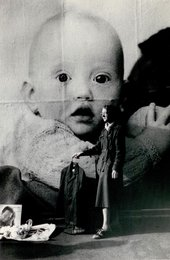 a black and white photograph of a woman standing in front of a large image of a babe