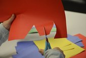 Photograph of a child's hands cutting coloured paper