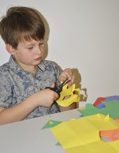 Kid cutting paper to make his collage
