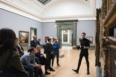 Members stand and listen to a talk in Tate Britain