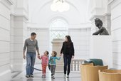 A man and woman hold hand in hand with two children in the Tate Britain Members room