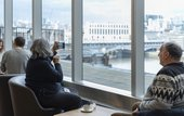 A woman sits and takes a photograph of the view from the members bar