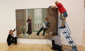 Three art handlers installing a painting