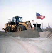 A woman placing an American flag on a sandy bank