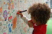 Six year old Jude drawing on cartoon drawings in the Moshi Monsters studio London