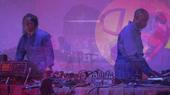 Men in boiler suits performing a DJ set