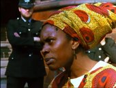 Film still of an woman wearing an African headscarf
