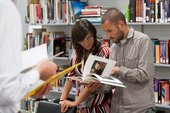 Two people in the archive looking at a book