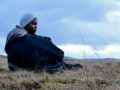 Young black person sat on a hill