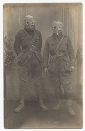 Black and white photograph of two soldiers wearing gas masks.