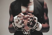 A close up images of a male's hands in chains