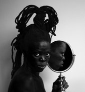 Black and white photo of the artist holding a mirror