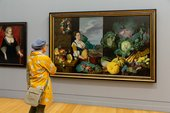 A person looks at a large painting featuring a woman and many vegetables