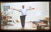 Film still of Bruce Nauman walking through his studio