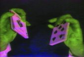 two fluorescent green hands holding fluorescent pink playing cards.