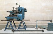 A piece of heavy machinery on a trestle bench on a plinth in a gallery