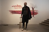 Artist Nikhil Chopra stands in front of his mural, drawn in different shades of red lipstick on a white wall. Chopra wears heavy eyeliner, and is dressed with reference to an Elizabethan bard in a corseted jacket, velvet cloak, tights, and heeled shoes.