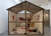 Nikhil Chopra, wearing only black underpants, leans against a wire cage that covers one side of a single-room structure, constructed inside a gallery space. The interior walls are covered in red murals; paint pots and clothing are scattered on the floor.