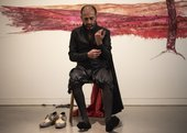 Nikhil Chopra sits on a chair in front of his red mural, his shoes removed and set to one side, one arm raised as he unbuttons one cuff. His gaze is directed to the floor, appearing contemplative.