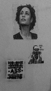 a wall with three pinned up images, including a portrait of a woman
