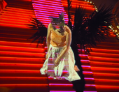 film still of person with animal mask on against stairs