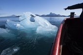 Photograph of a boat and an iceberg floating in Nuup Kangerlua, Greenland