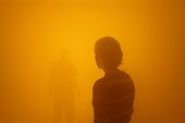 a woman stands in an orange mist