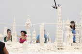 People sit and make buildings out of white lego pieces