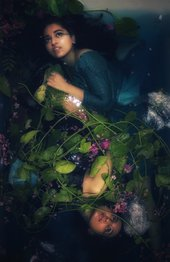 Photograph of lady underwater surrounded by flowers