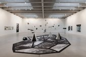 Installation view of the exhibition including large black and white patterned carpet with small sculptures on it