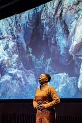 Artist Otobong Nkanga stands with her hands on her abdomen, fingers interlaced, breathing deeply with chin raised. Behind her is a projected image of a rocky landscape