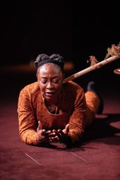 Otobong Nkanga lies on the stage, on her front, resting on elbows, palms upwards. She looks down at her hands, her mouth open as if speaking, a pained or worried look on her face. The horizontal pole with model trees is visible to the right of her head
