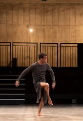 a man stands with right leg lefted in an empty auditorium