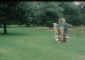 Film still of a person covered in fabrics walking on a lawn