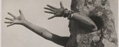 sepia phtograph of arms reaching out of a rock like suit
